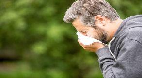 Homem limpando o nariz