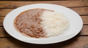 Prato com arroz e feijão sob superfície de madeira