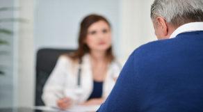 Homem grisalho, de costas, sendo atendido por médica