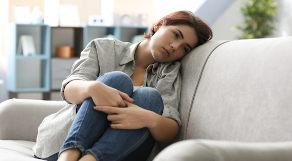 Mulher encolhida em sofá com expressão de tristeza