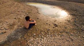 Menina sentado em solo seco e rachado e ao lado de uma pequena poça de água