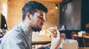 Homem segurando sanduíche, prestes a comer