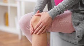 Mulher segurando o joelho com as duas mãos