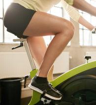 Mulher pedalando em bicileta ergométrica