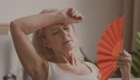 mulher idosa com calor e segurando leque