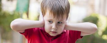 Criança com as mãos nas orelhas