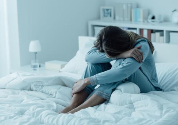Mulher triste em cima da cama