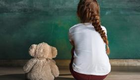 Criança sentada ao lado de ursinho
