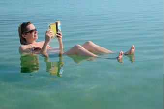 Mulher lê um livro flutuando nas águas do Mar Morto, em Israel