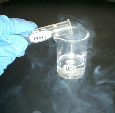 Reação entre o gás cloreto de hidrogênio e o gás amônia, formando o sal cloreto de amônio (vapor branco)