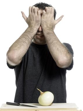 Homem chorando ao cortar cebola